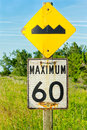 Road signs bump and maximum two on a wooden post the top yellow one is a warning sign for a in the raod the bottom black white one Royalty Free Stock Image