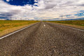 Road steppe sky straight asphalt with marking surrounded by in the altai russia with mountains at the horizon and cloudy blue Stock Image