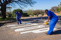 Road stop sign maintenance painting municipal team repairing worn out and lines with new coat of paint durban suburb south africa Stock Images