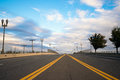 Road with street lights and dividing strip receding cloudy horiz multiband wide asphalted a oncoming traffic marked by the yellow Royalty Free Stock Images