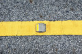 Road stud with yellow reflector on the yellow line of asphalt Stock Photo