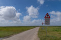 The road to Mandø, Denmark with warning sign of tidal water