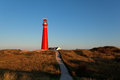 Road to red lighthouse and blue sky netherlands Royalty Free Stock Photography