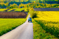 Road with tractor in a beautiful region with flower meadows and fields. Slovakia, Central Europe, Liptov.
