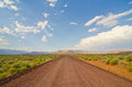 The road less traveled a cutting through arizona desert scrubland Royalty Free Stock Image
