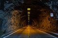 Road through tunnel illuminated a hewn out of rock with white lines at left and right sides and double yellow line in the center Royalty Free Stock Image