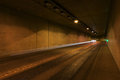 Road through tunnel at night lighted receding Stock Image