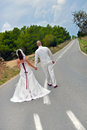 On the road two lives coming together bride and groom walking become one lines become one line to future concept for Royalty Free Stock Photography