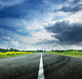 Road view on sunny summer day with dramatic clouds Royalty Free Stock Photo