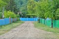 Road in the village empty with fences of houses left and right Royalty Free Stock Images