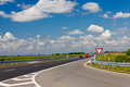 Road winding through green fields blue sky white clouds Royalty Free Stock Photography
