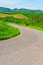 Road winding paved between spring plowed fields in the tuscany Royalty Free Stock Photo
