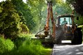 Road work in progress mowing grass along roadside verge with tractor Stock Photos