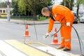 Road worker marking pedestrian crossing line