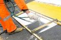 Road worker marking street lines zebra crossing