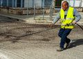 Road worker spraying bitumen emulsion with the hand spray lance before applying a new layer of asphalt Stock Photos