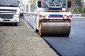 Road works asphalting and laying fresh bitumen during construction works industrial heavy compactor duty Royalty Free Stock Image