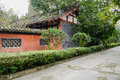 Roadside aged chinese building with enclosure in trees and shrub red shrubs chengdu china Royalty Free Stock Images