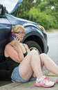 Roadside assistance woman calling for help young blonde with congenital abnormality symbrachydactyly of left hand calls from side Royalty Free Stock Photography