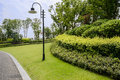 Roadside streetlamp and garden in cloudy summer verdant on day Stock Images