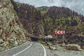Roadside warning triple chevron sign picturesque mountain landscape with for dangerous road turn on sinuous transfagarasan highway Stock Photography