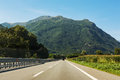 Roadway to the mountains straight in a sunny day Stock Image