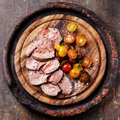 Roast beef with cherry tomatoes on cutting board Stock Image