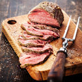 Roast beef on cutting board and meat fork Royalty Free Stock Photo