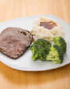 Roast beef potatoes and broccoli a dinner of sliced mashed with gravy fresh on a white plate on wood table Stock Image