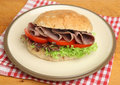 Roast beef roll sandwich on plate tomato and lettuce in a granary bread Stock Photo