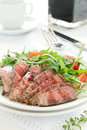 Roast beef with salad of arugula and tomatoes Royalty Free Stock Photos