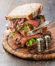 Roast beef sandwiches with lettuce on wooden cutting board on dark wooden background Stock Photo