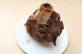Roast beef shank on a white plate Royalty Free Stock Image