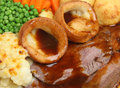 Roast beef sunday dinner traditional with yorkshire puddings and gravy Stock Images
