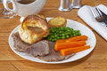 Roast beef and yorkshire pudding with gravy potatoes peas carrots Royalty Free Stock Image