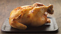 Roast chicken on brown wooden plate Stock Photography