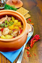 Roast chicken in a clay pot on a napkin with meat potatoes and peppers spoon crispbreads dill wooden board Stock Photos