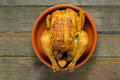Roast chicken grilled served in a clay pot and on a rough wooden table Stock Image