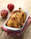 Roast chicken and two red apples on wooden table Royalty Free Stock Photography