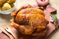 Roast chicken on wooden board with potatoes and ketchup photographed with natural light selective focus focus on the front of the Stock Photo