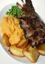 Roast lamb rack potato peas Royalty Free Stock Images