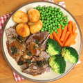 Roast lamb sunday dinner with mint sauce vegetables gravy and Royalty Free Stock Images