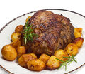 Roast leg of lamb plate with potatoes and rosemary on white background Royalty Free Stock Photos