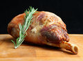 Roast leg of lamb shallow dof focus in centre image on herb Royalty Free Stock Photography