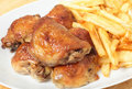 Roast lemon chicken thighs and fries Stock Photography
