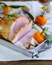 Roast pork with mushrooms and tangerines festive dish Stock Photo