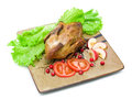 Roast wild duck carcass on white background with lettuce tomatoes apples and cranberries a plate fone gorizontalnoe photo Stock Images