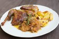 Roasted or baked Guinea fowl served with baked potatoes and sweet onion with apples and raisins.