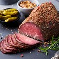 Roasted beef, pastrami on slate cutting board. Close up. Royalty Free Stock Photo