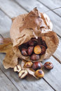 Roasted chestnut in a papper bag on old wooden table Royalty Free Stock Photography